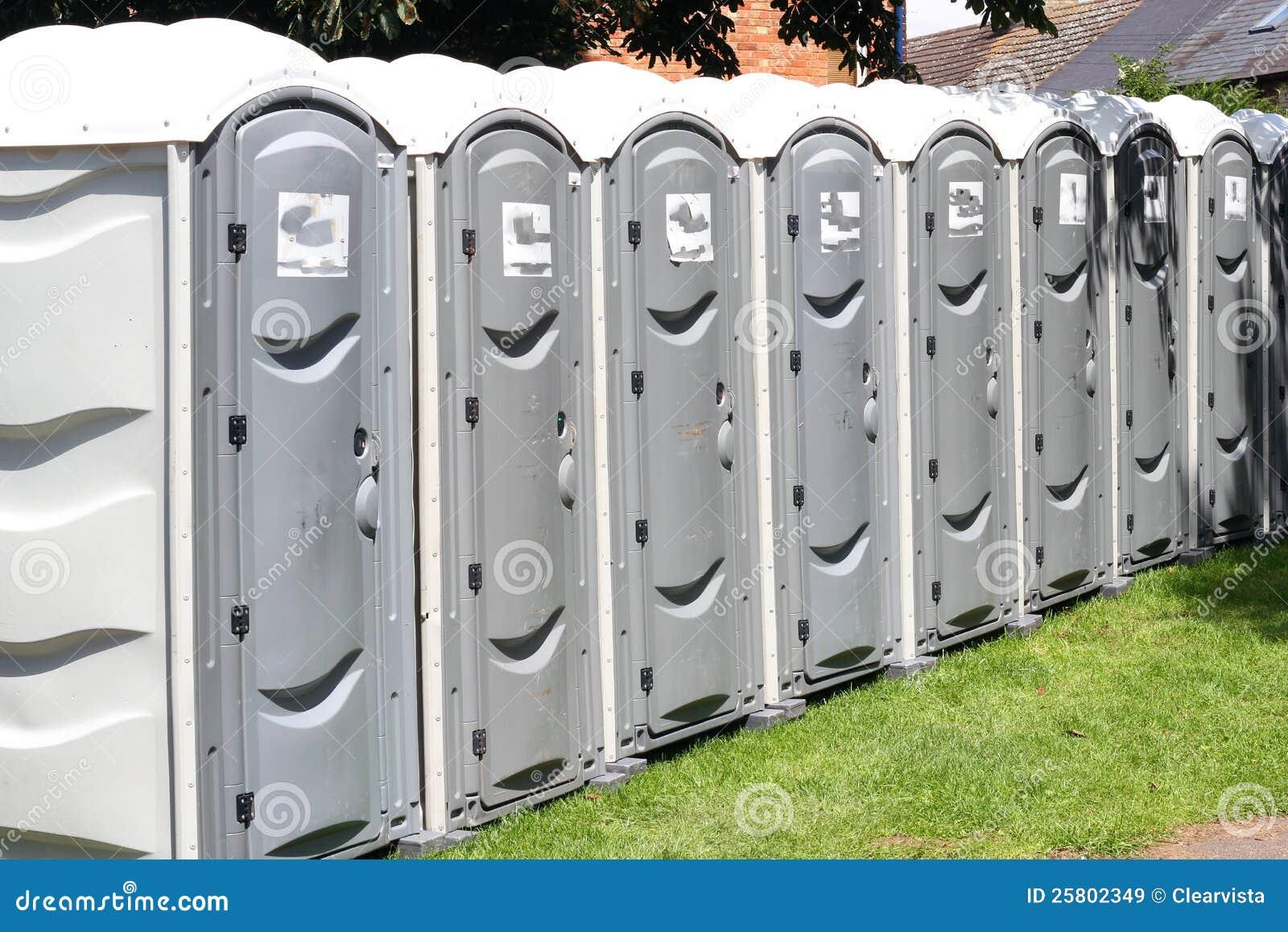 Rad av bärbara utvändiga toaletter.