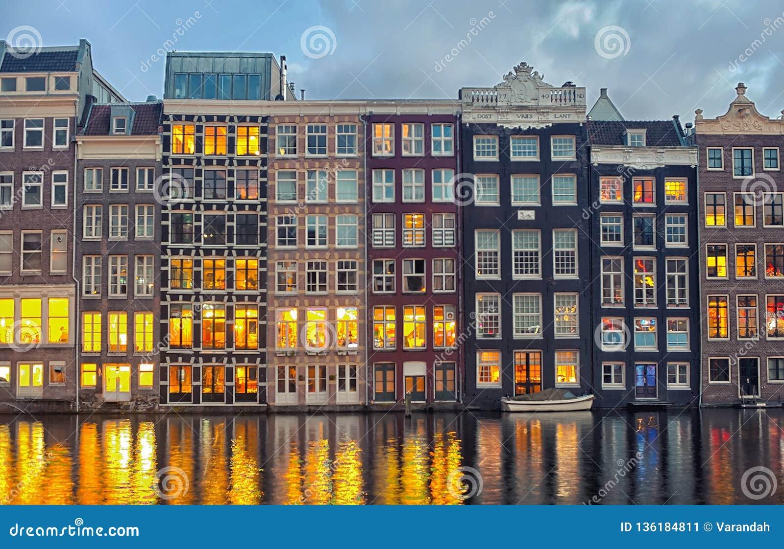 Rad av holländska hus på den centrala kanalen Damrak Amsterdam, Nederländerna på skymning