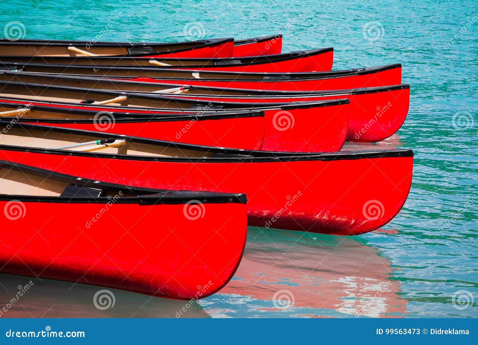 Rad av röda kanoter i sjön