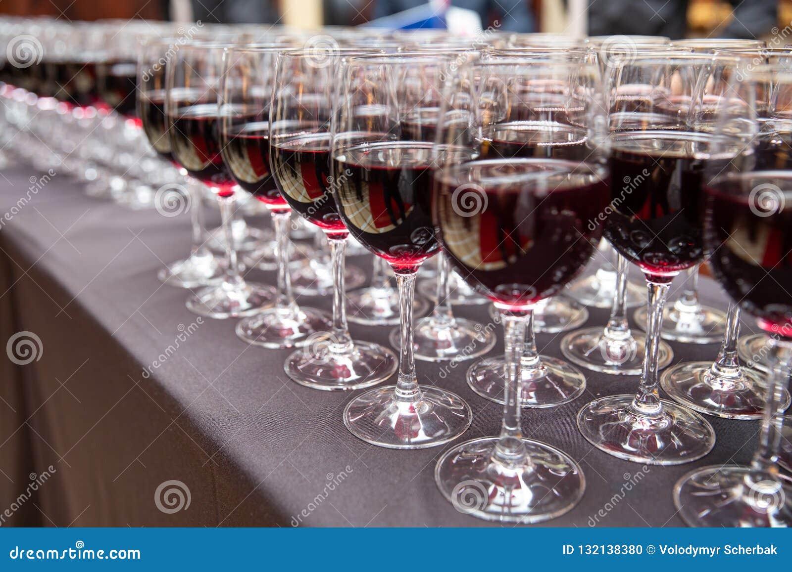 Rader av rött vinexponeringsglas för parti och bröllop