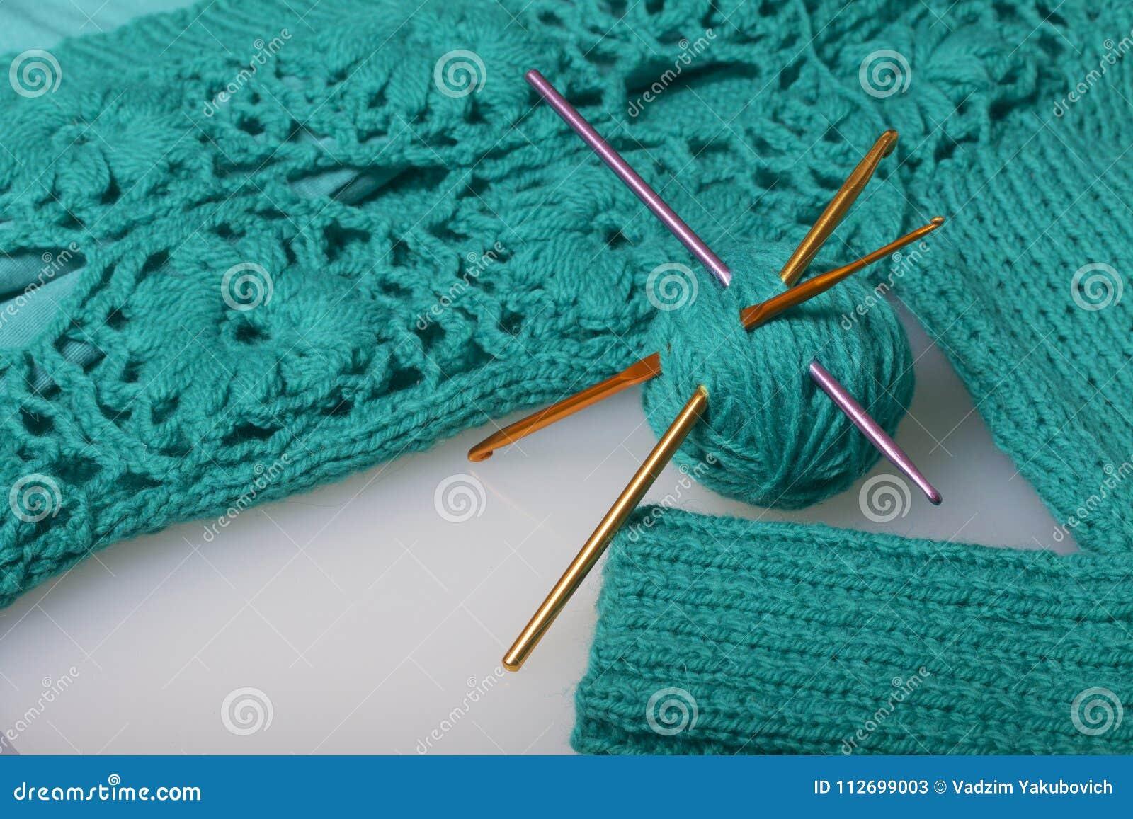 Rader av tråden för att sticka smaragden färgar och krokar för att sticka Lögn på en klar stucken produkt