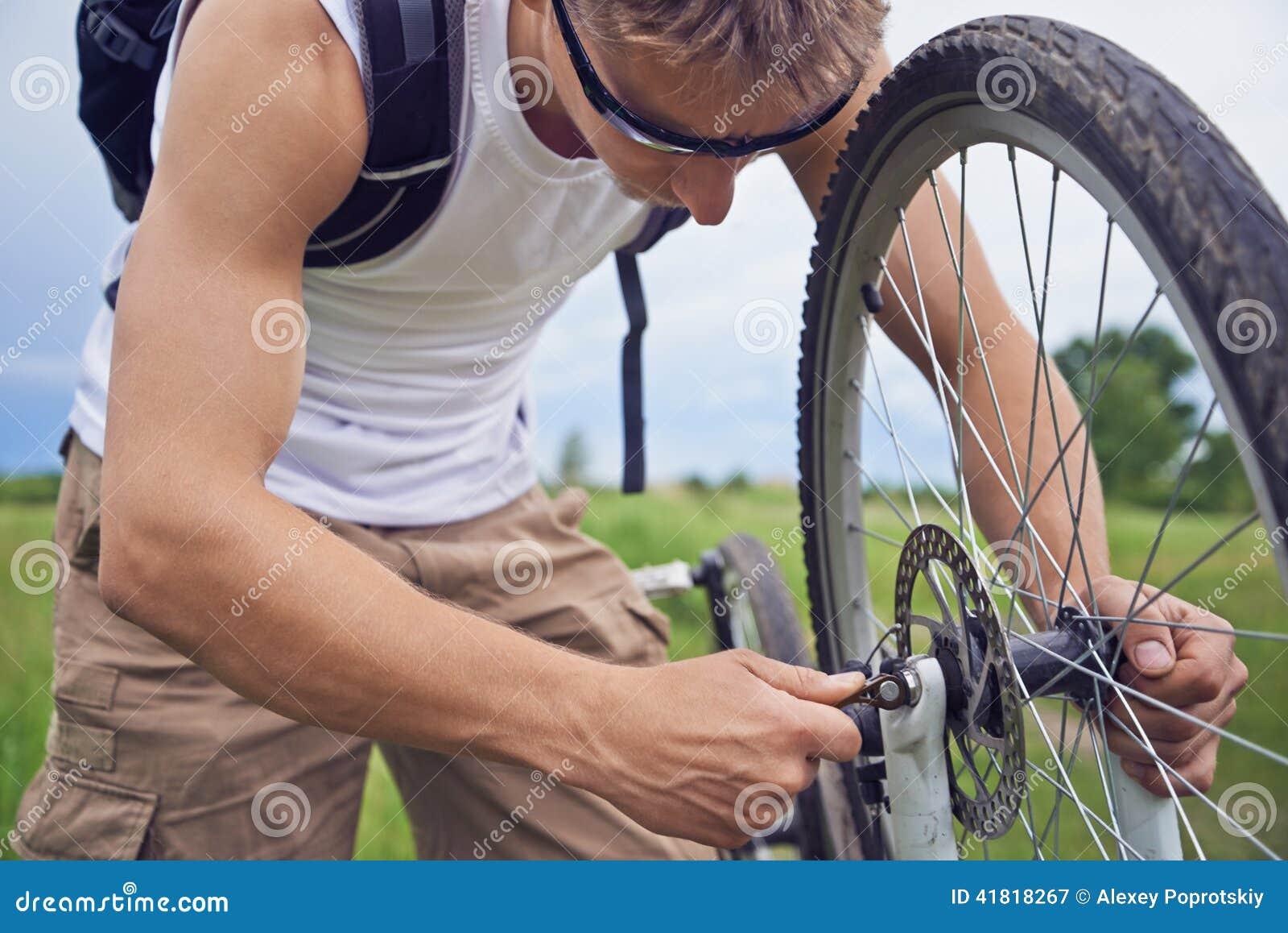 Radfahrer überprüft Bremsrad des Fahrrades