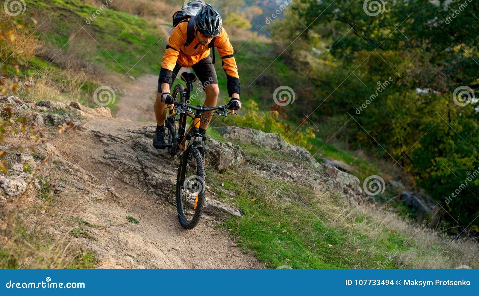 Radfahrer in der Orange, welche die Mountainbike auf Autumn Rocky Trail reitet Extremer Sport und radfahrendes Konzept Enduro