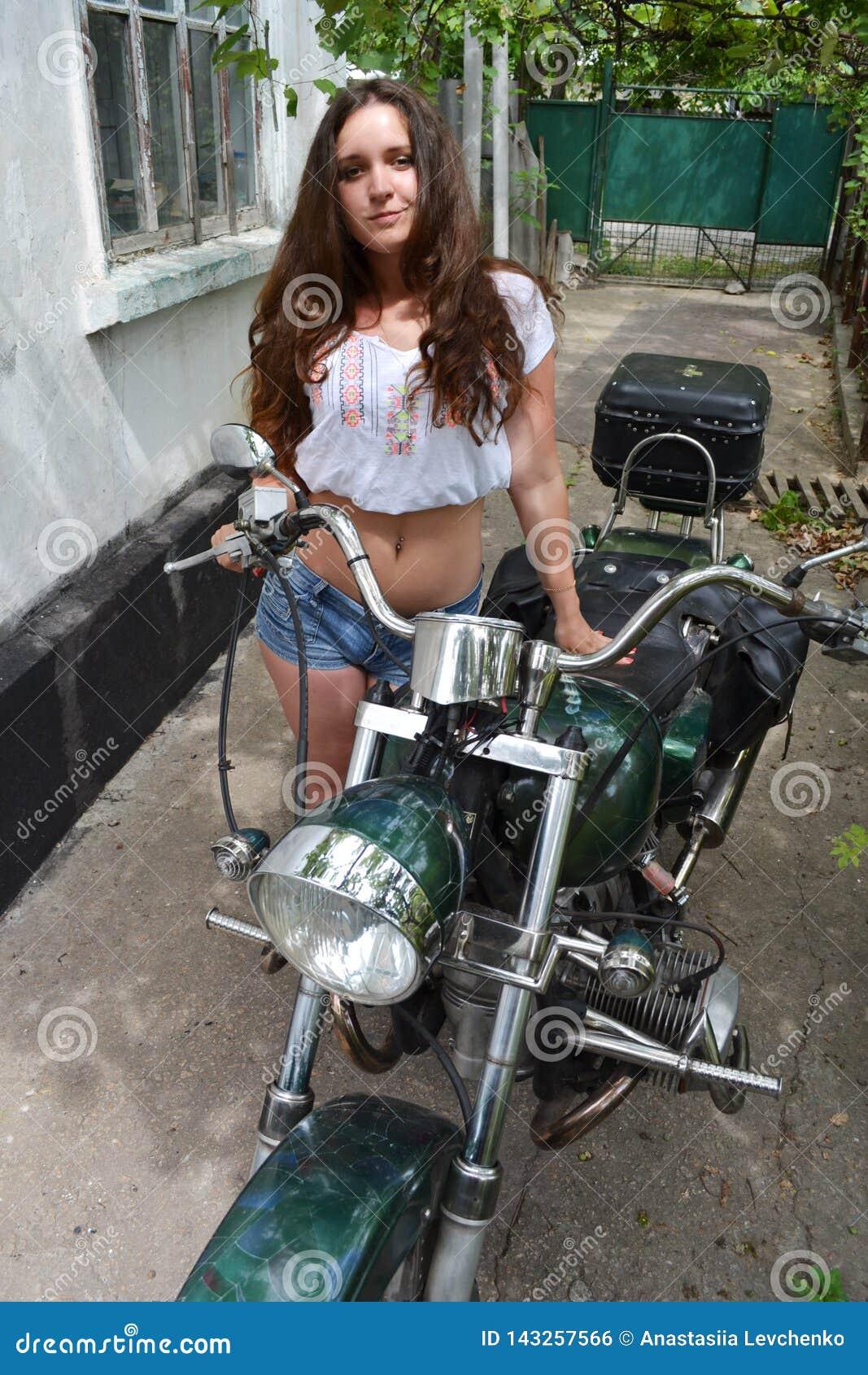 Radfahrermädchen, das auf kundenspezifischem Motorrad der Weinlese sitzt Lebensstil im Freien tonte Porträt