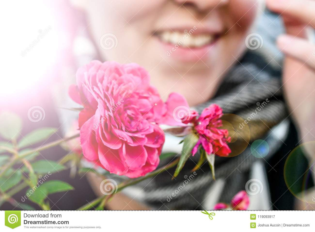 A radiant pink flower held by a smiling happy woman who appears to be cold.