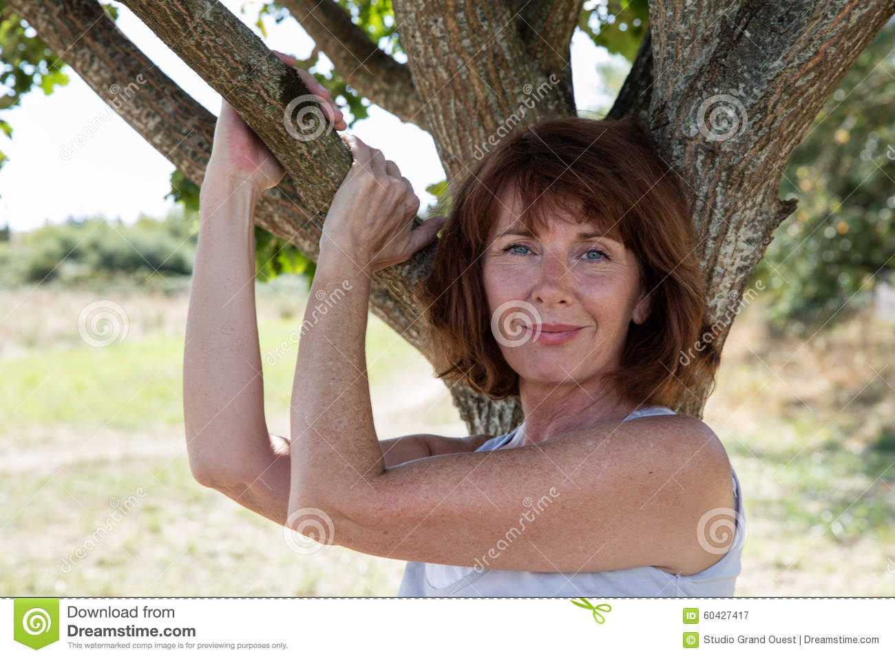 Radiant Young Aging Woman Touching A Tree With Sensuality