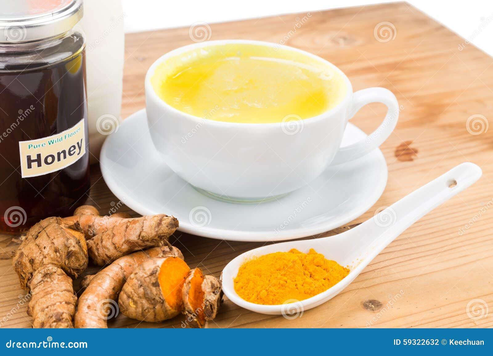 Radici di curcuma con le bevande del miele e del latte per bellezza e salute