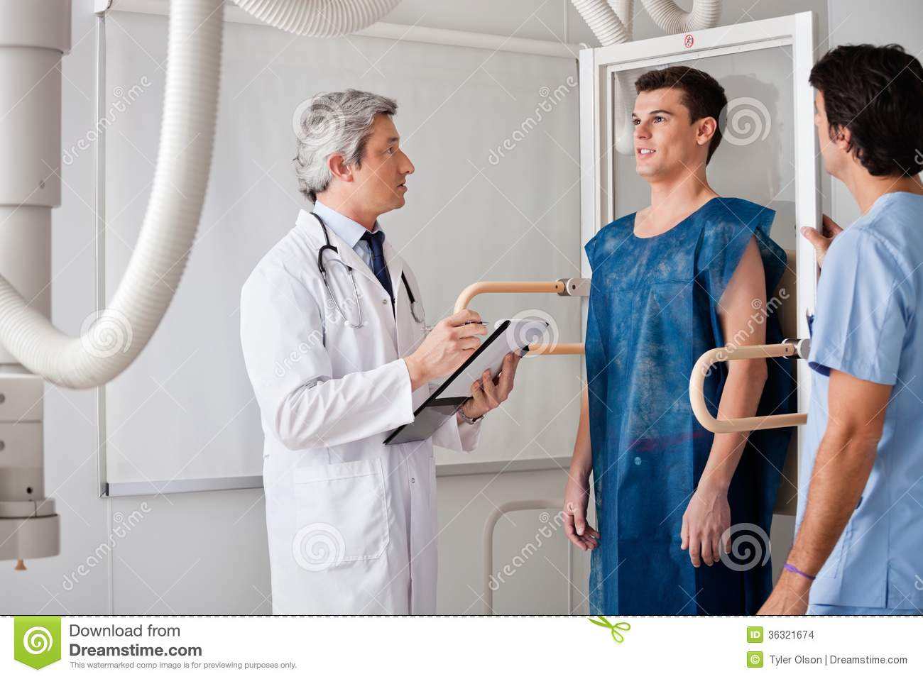 radiologists conducting x-ray on male patient stock photo - image of