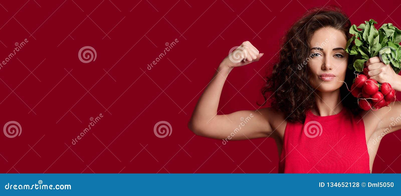 Radis frais de jeune de sport prise assez gaie de femme avec les feuilles de vert et le doigt de pointage dieting