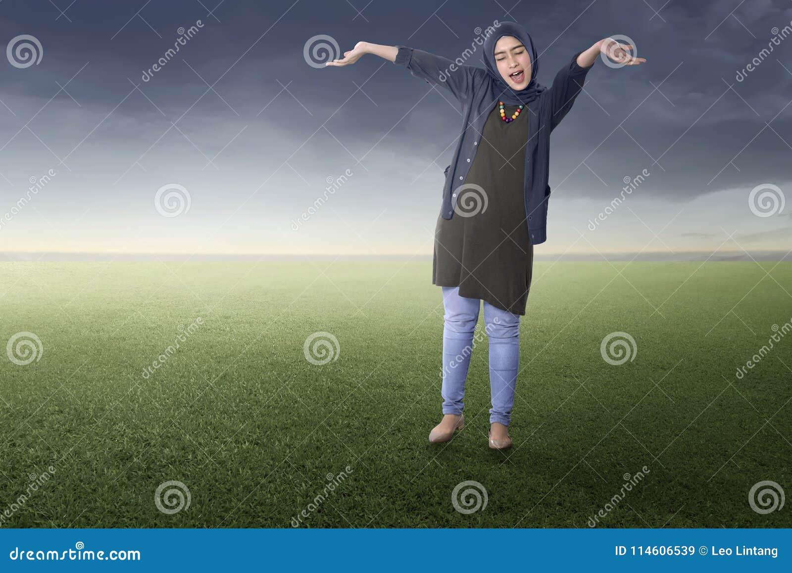 Radosna azjatykcia muzułmańska kobiety pozycja