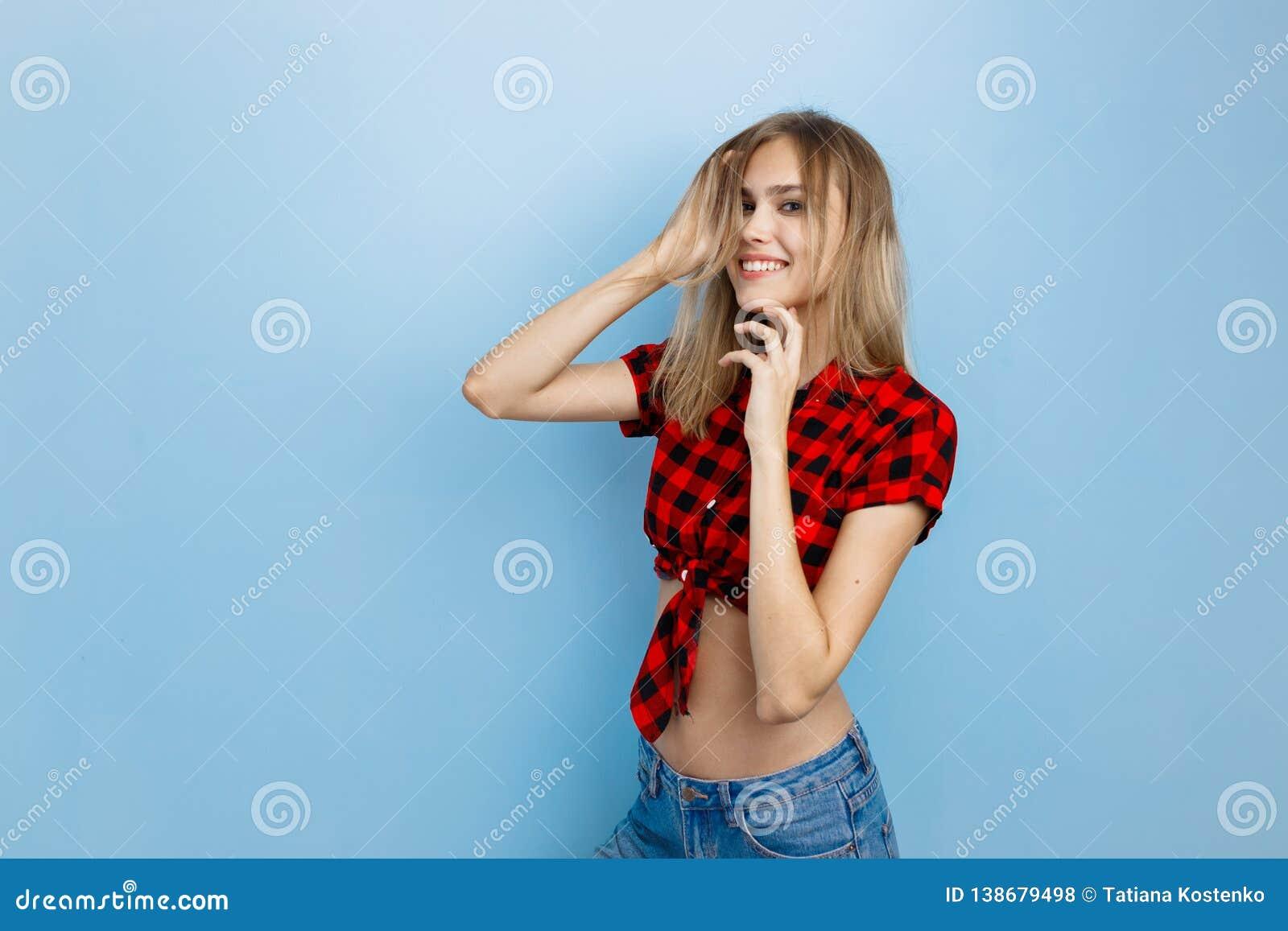 Radosna piękna młoda blond dziewczyna jest ubranym czerwoną w kratkę koszula i niebieskich dżinsy ono uśmiecha się z niebieskimi