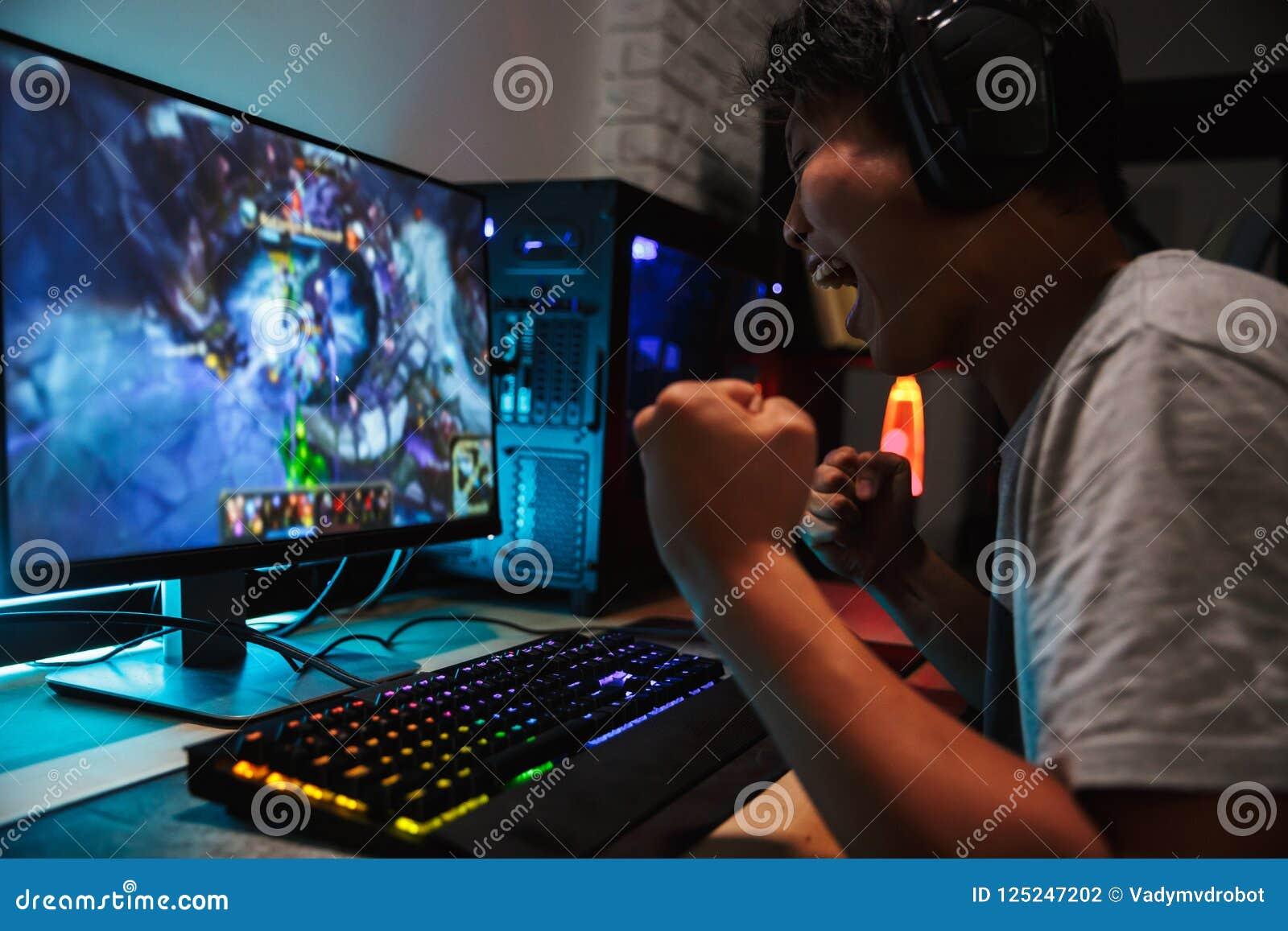 Radosny azjatykci nastoletni gamer mężczyzna bawić się wideo gry na komputerze w d
