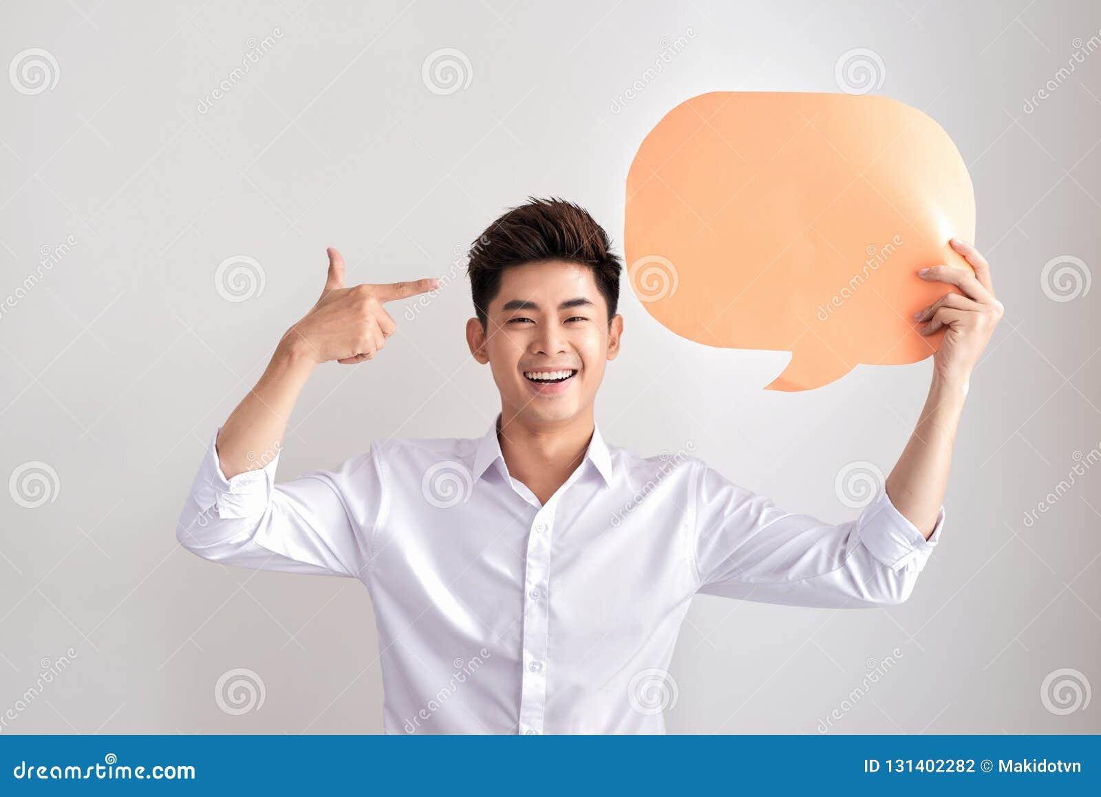 Radosny główkowanie mężczyzna trzyma biel mowy pustego balon z przestrzenią dla teksta odizolowywającego na białym tle