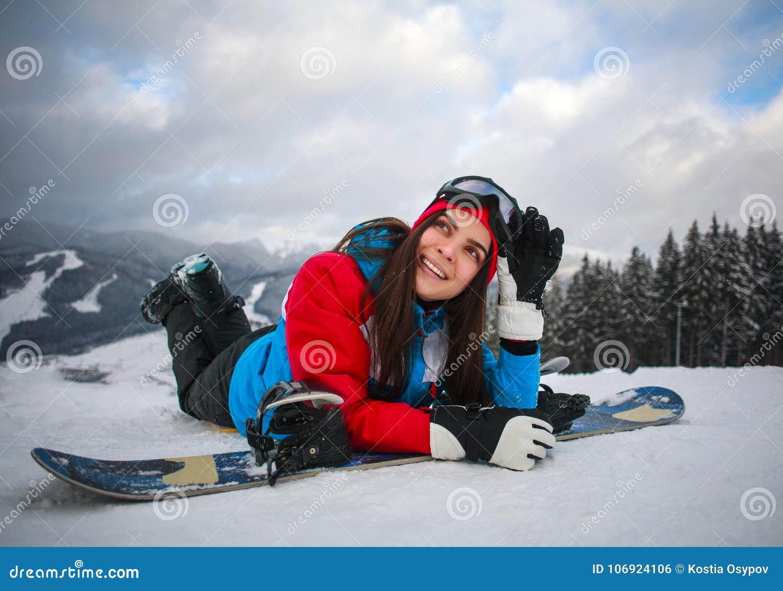 Radosny kobiety snowboarder w zimie przy ośrodkiem narciarskim