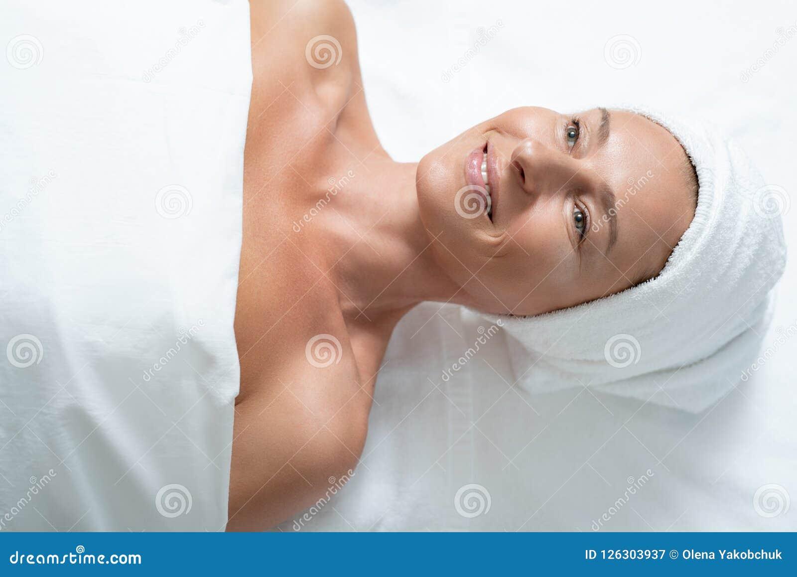 Radosny w średnim wieku kobiety lying on the beach na masażu stole