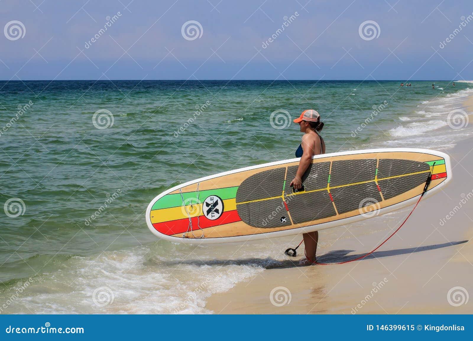 Radschaufel der Surfer-Holding-Dreiergruppen-X auf dem Strand