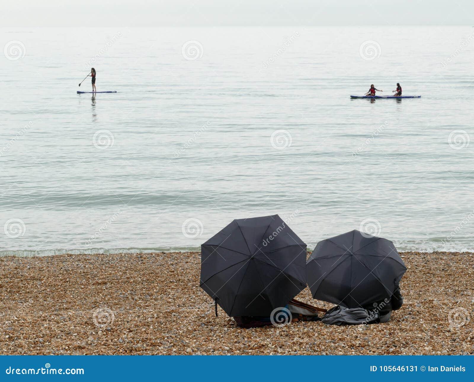 Radschaufel und Kajaks auf Meer mit zwei Regenschirmen im Vordergrund