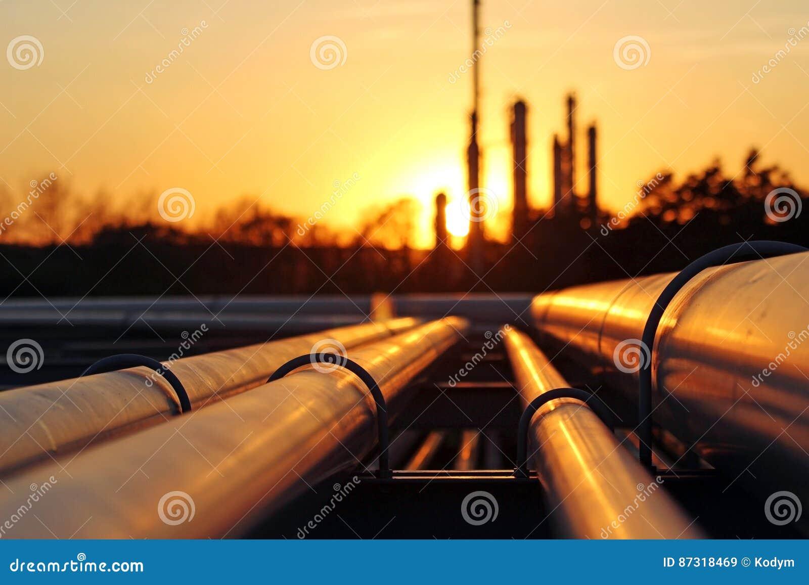 Raffinerie de pétrole brut pendant le coucher du soleil avec le conection de canalisation