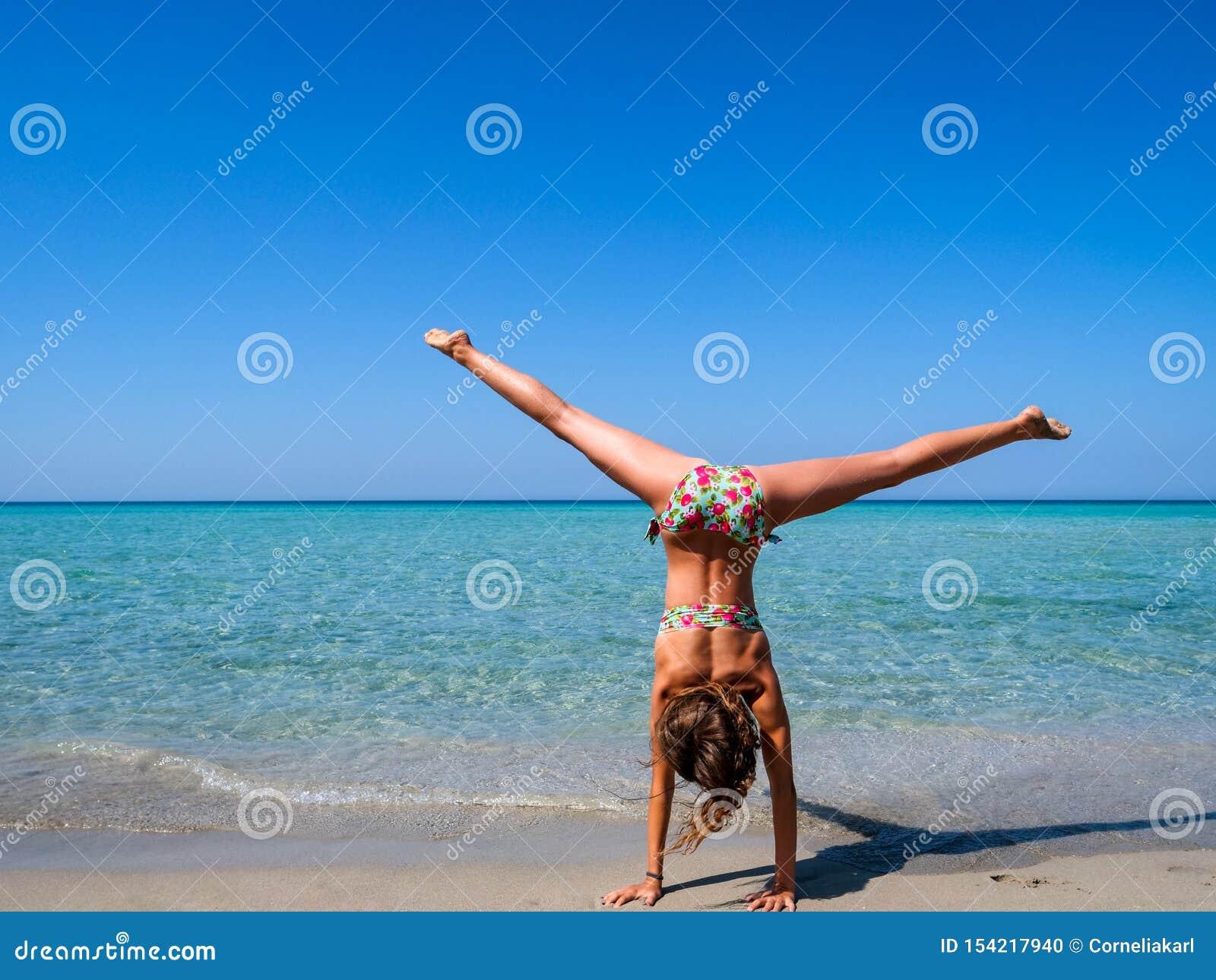 Adolescente Che Fa Cartwheel Che Gioca Sulla Spiaggia