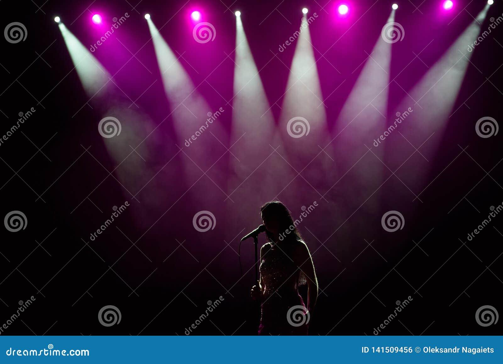 Ragazza in abito lungo che esegue in scena Ragazza che canta sulla fase davanti alle luci Siluetta della condizione del cantante