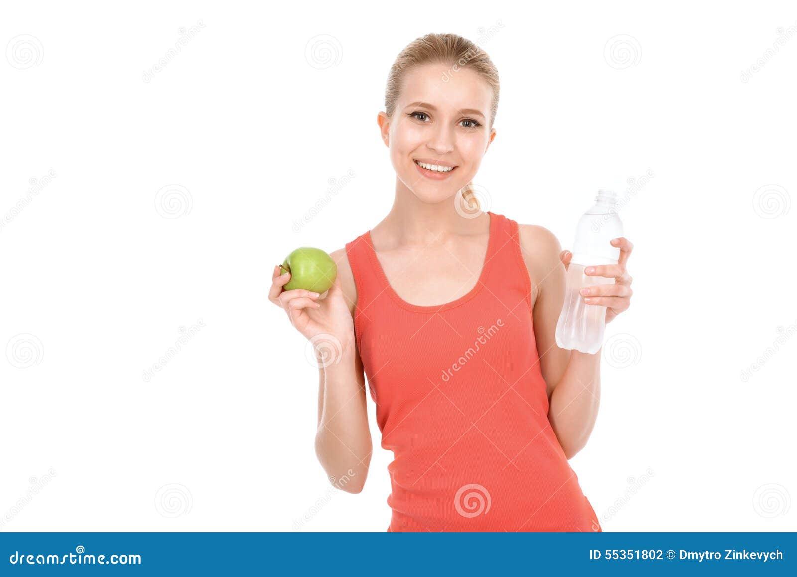Ragazza adatta con la mela ed acqua