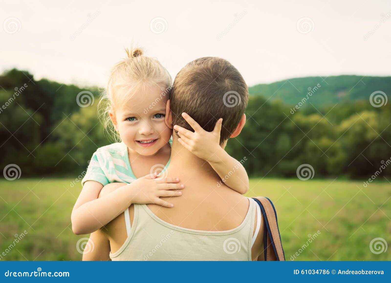 Ragazza adorabile che sorride e che abbraccia sua madre