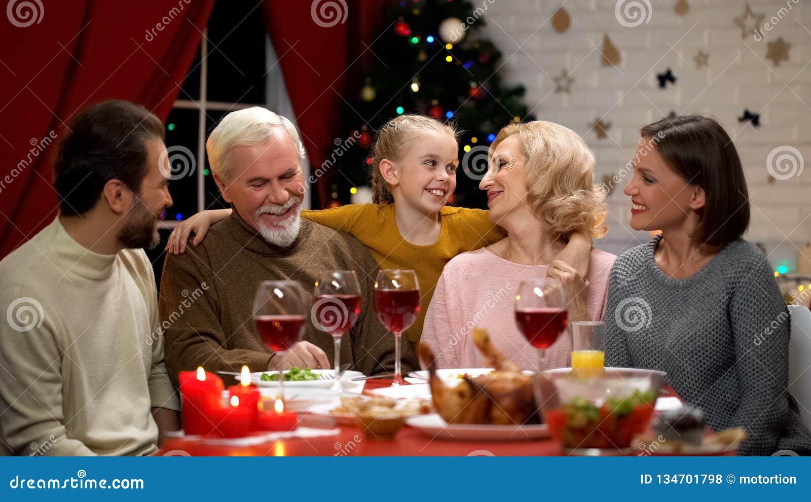 Ragazza adorabile felice che abbraccia i nonni, famiglia che ha cena tradizionale di natale