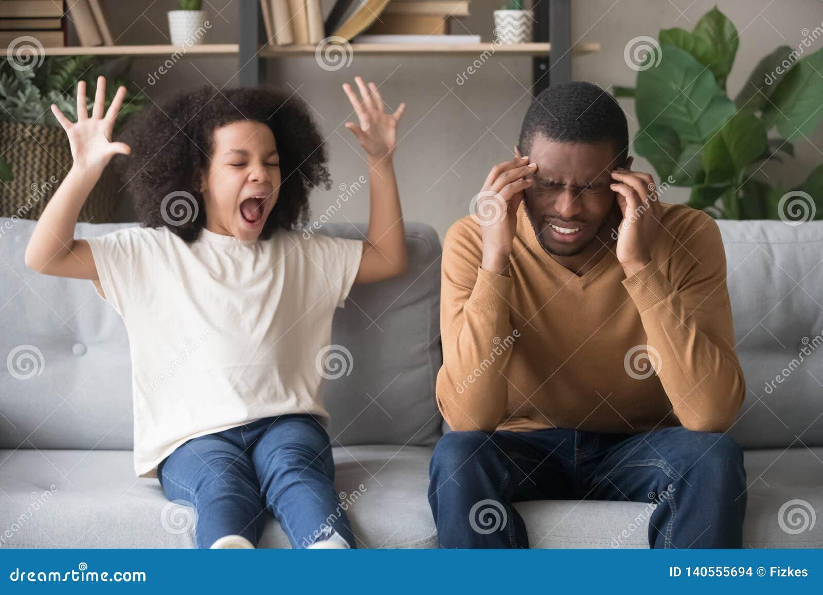 Ragazza africana testarda del bambino nel capriccio che grida al padre nero
