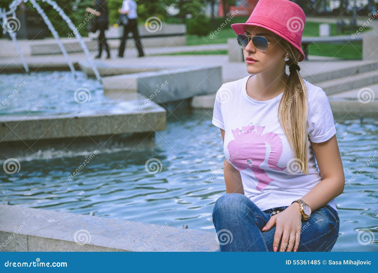 Ragazza alla moda che si siede dalla fontana