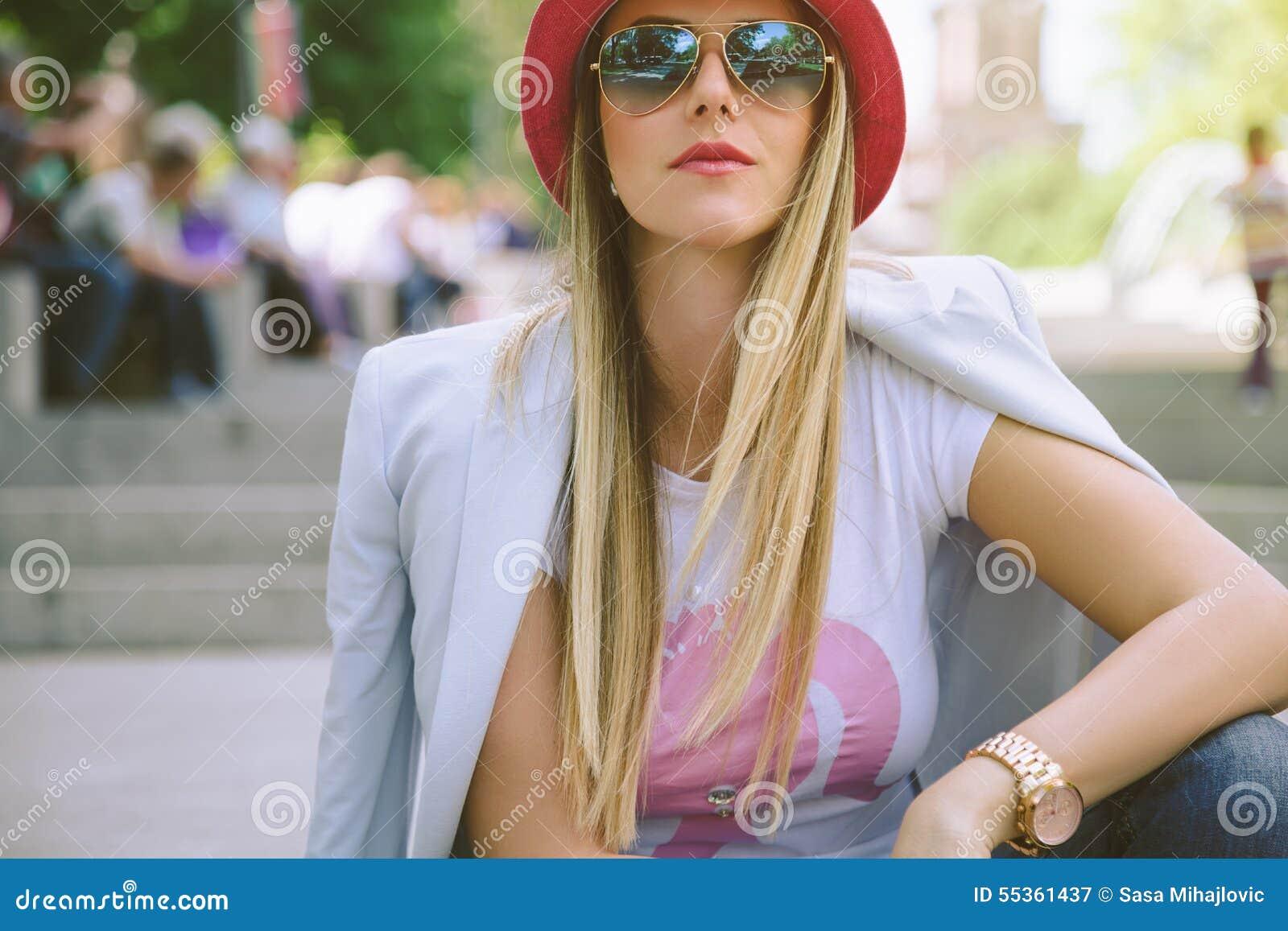 Ragazza alla moda che si siede sulle scale