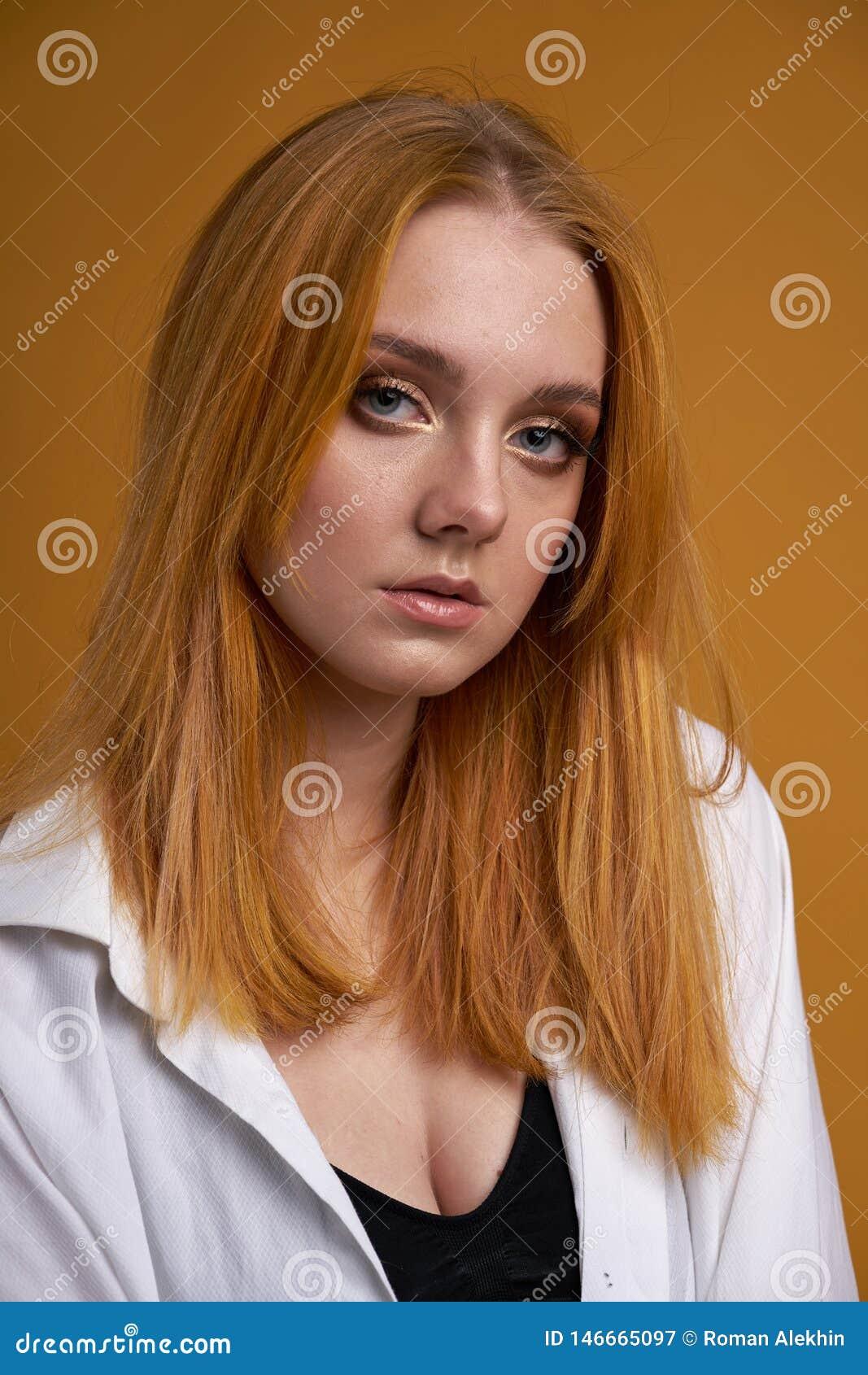 Ragazza alla moda con capelli ricci, sorridendo sveglio, posanti, sul fondo giallo