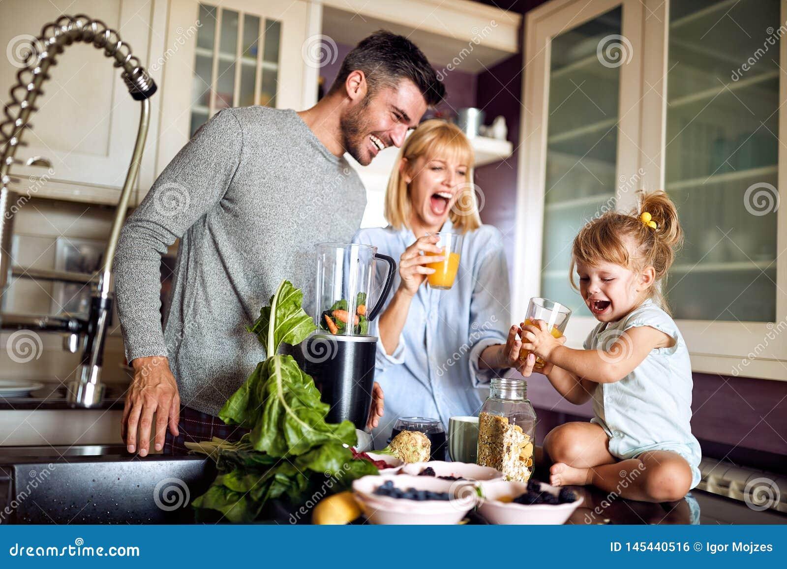 Ragazza allegra con i genitori in cucina