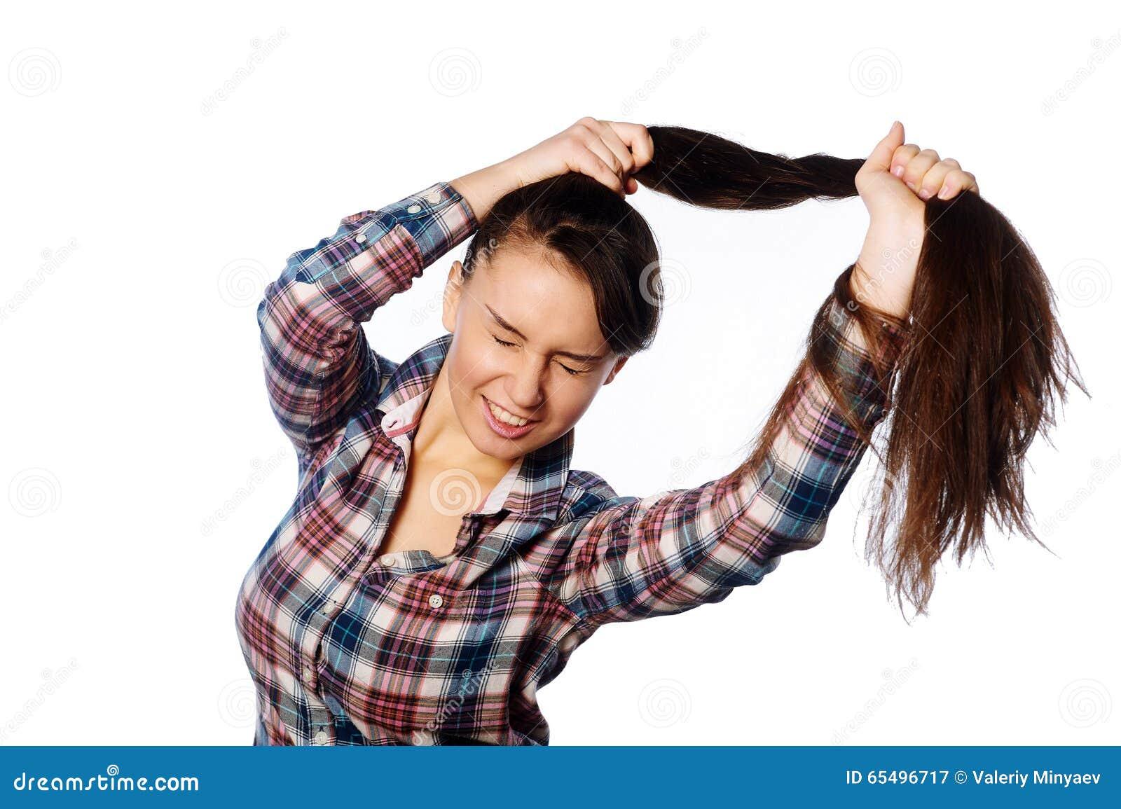 Ragazza allegra in modo divertente che tiene i suoi capelli lunghi in coda di cavallo sopra fondo bianco