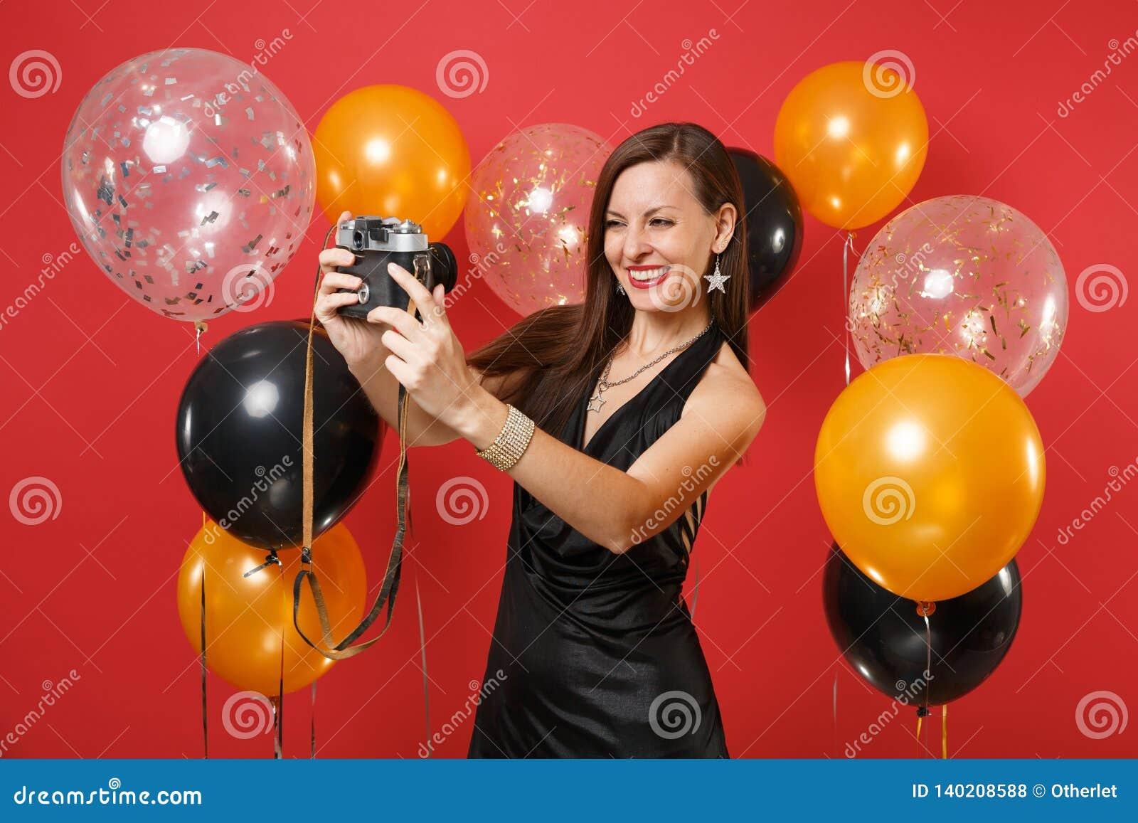 Ragazza allegra in poco vestito nero che fa prendendo selfie sparato sulla retro macchina fotografica d annata della foto su fond