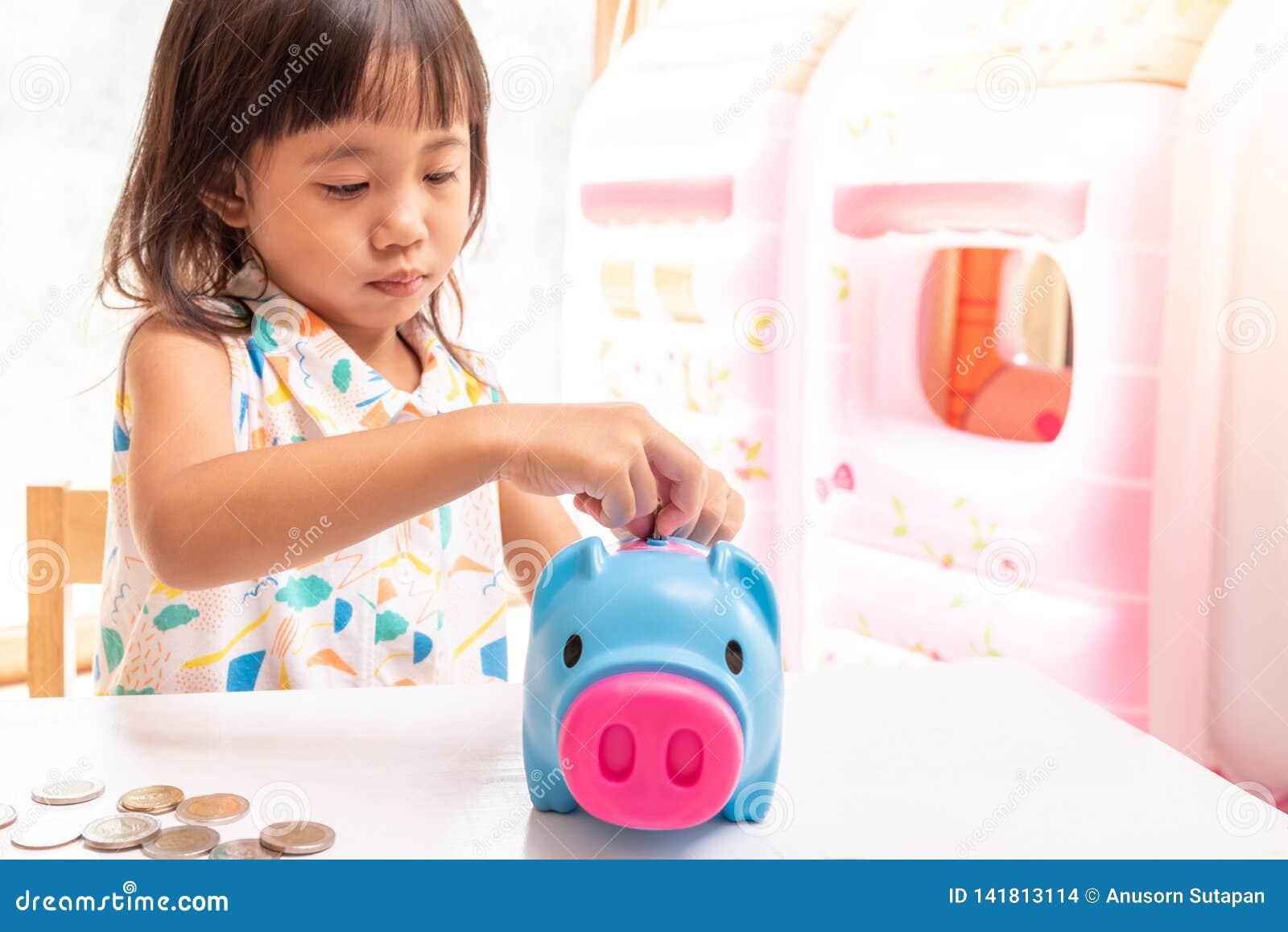 Ragazza asiatica che mette moneta nel porcellino salvadanaio per soldi di risparmio Fuoco selettivo della mano del bambino