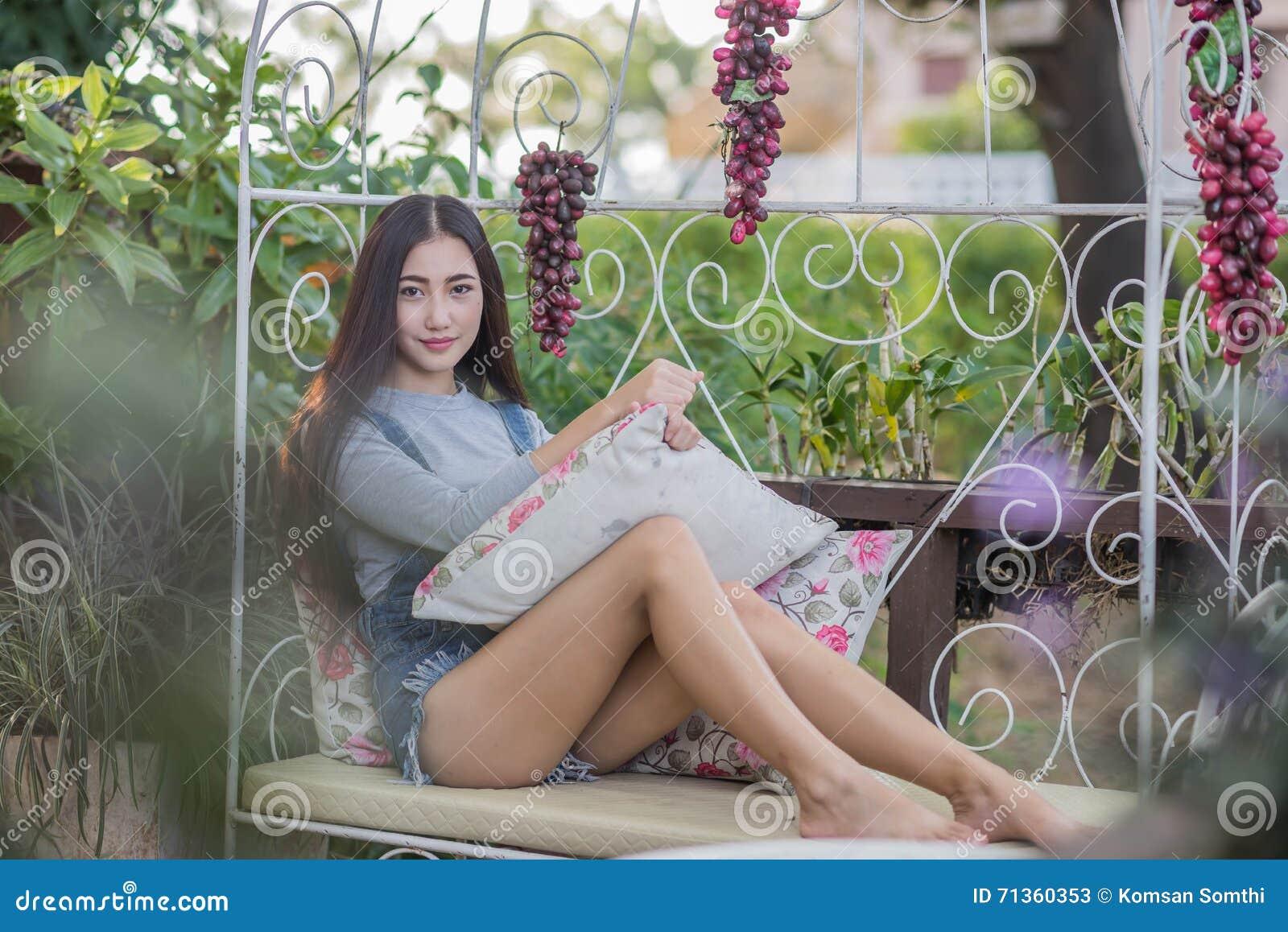 Ragazza asiatica che si siede sul sofà, rilassantesi