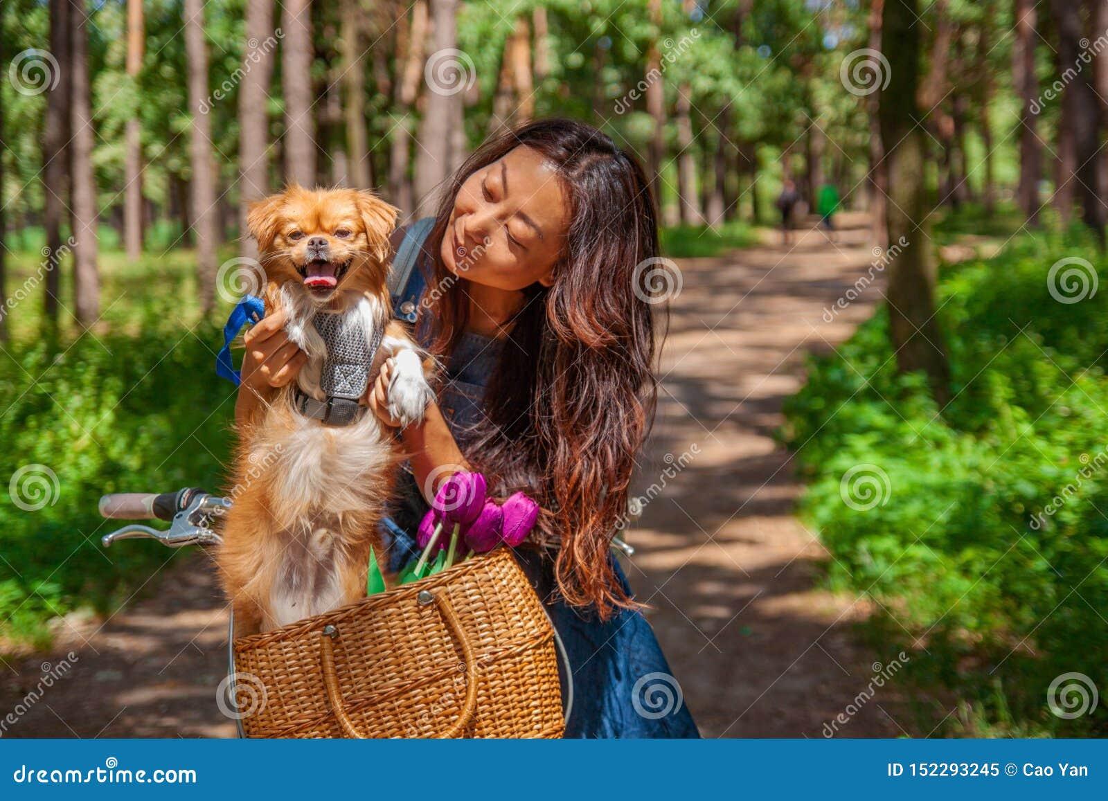 Ragazza asiatica sveglia con poco cane che cammina nel parco Donna che si siede sull erba verde con il cane - all aperto in ritra