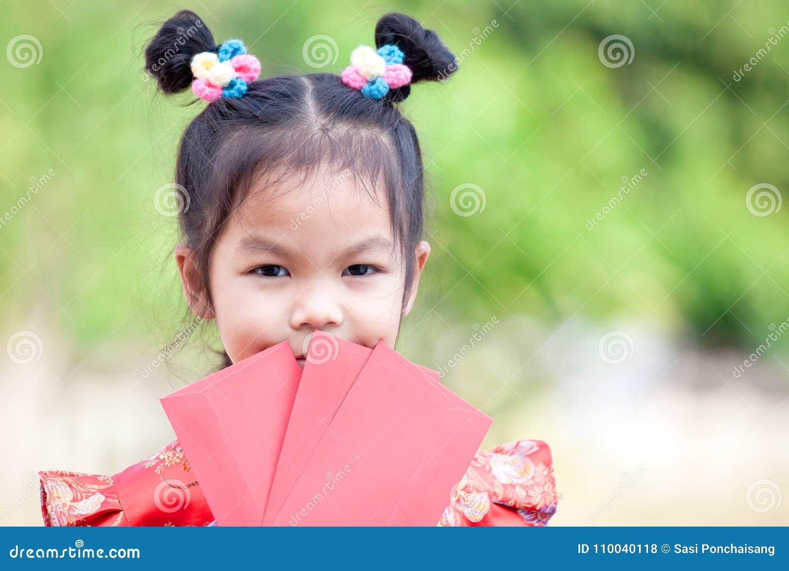 Ragazza asiatica sveglia del bambino che tiene busta rossa