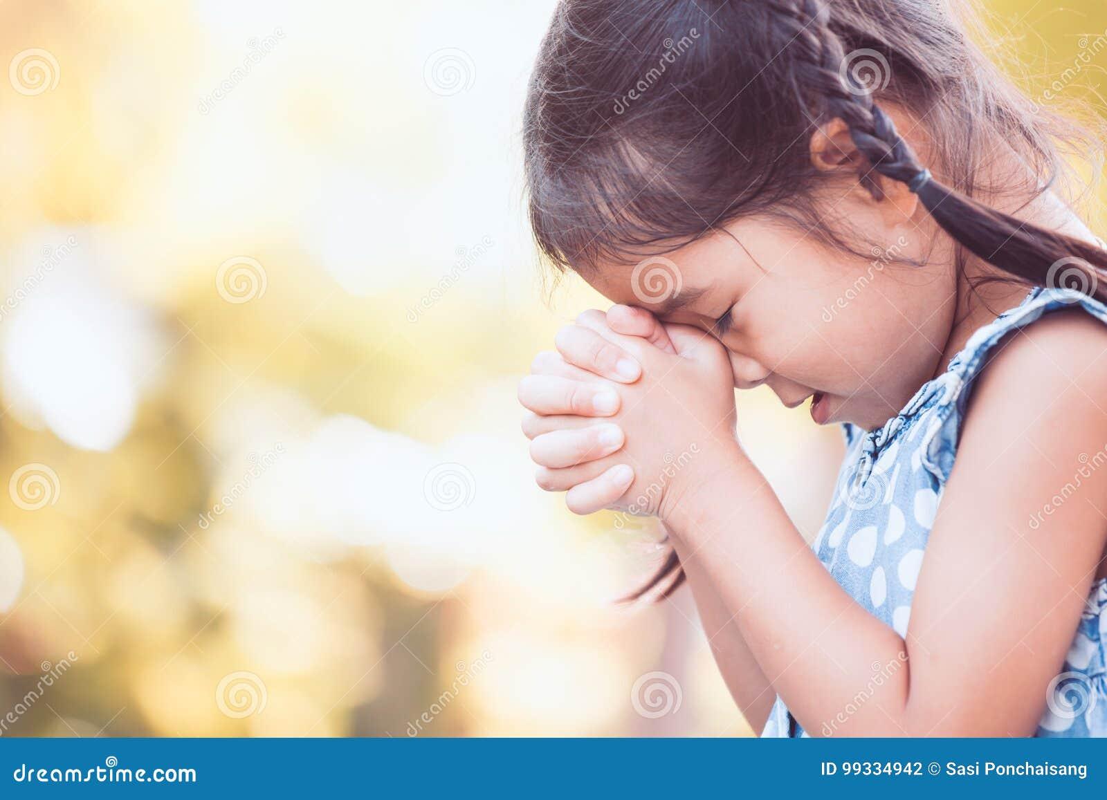 Ragazza asiatica sveglia del piccolo bambino che prega con piegato la sua mano