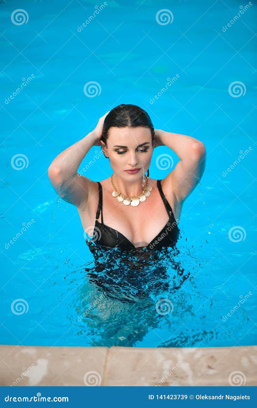 Ragazza attraente in bikini nel giorno di estate caldo dello stagno