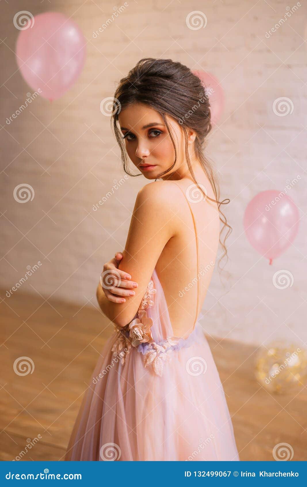 Ragazza attraente con capelli scuri in un acconciatura splendida, vestita in un rosa delicato lungo con un vestito porpora con