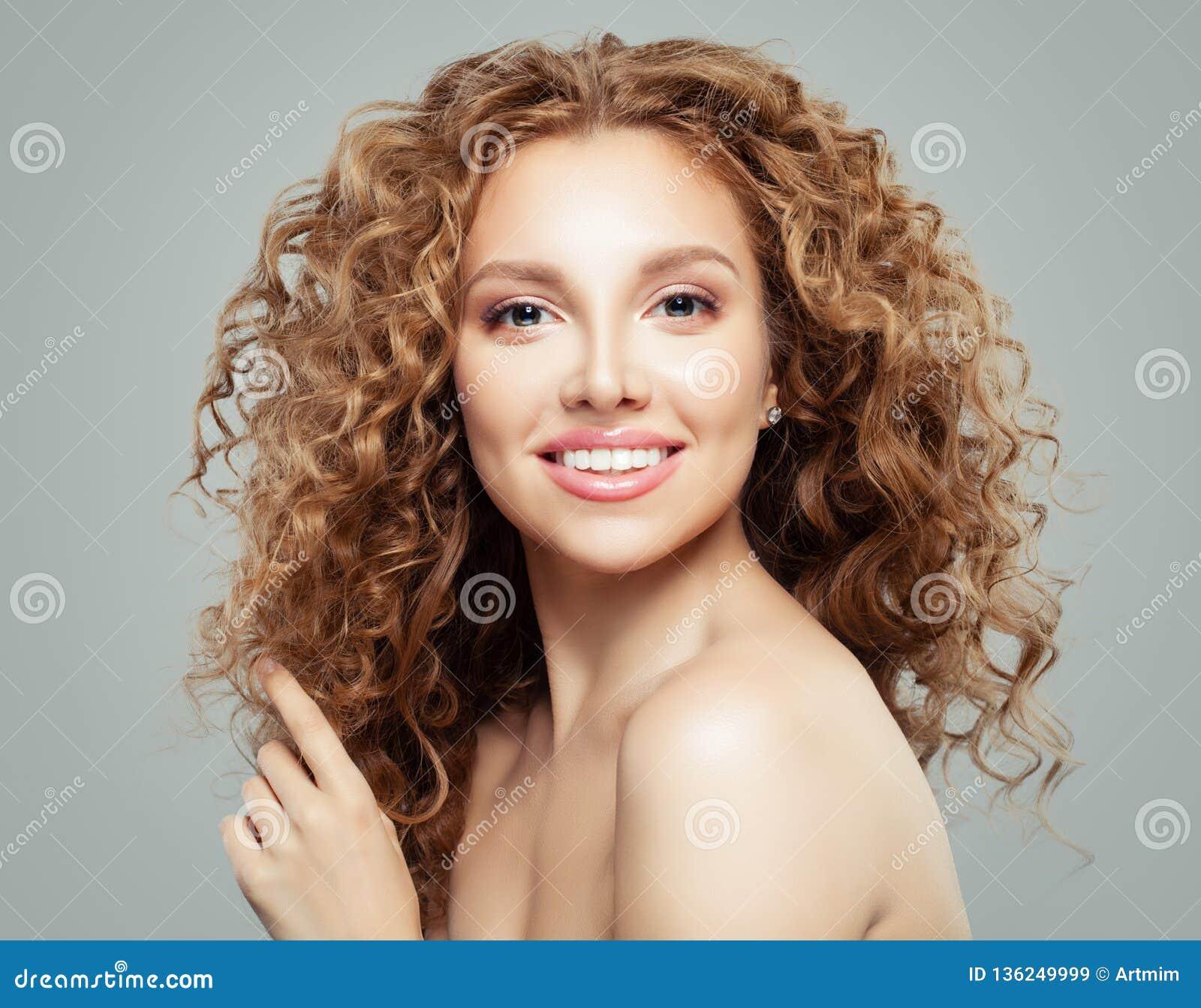 Ragazza attraente della testarossa con chiara pelle e capelli ricci sani lunghi Bello fronte femminile su fondo grigio