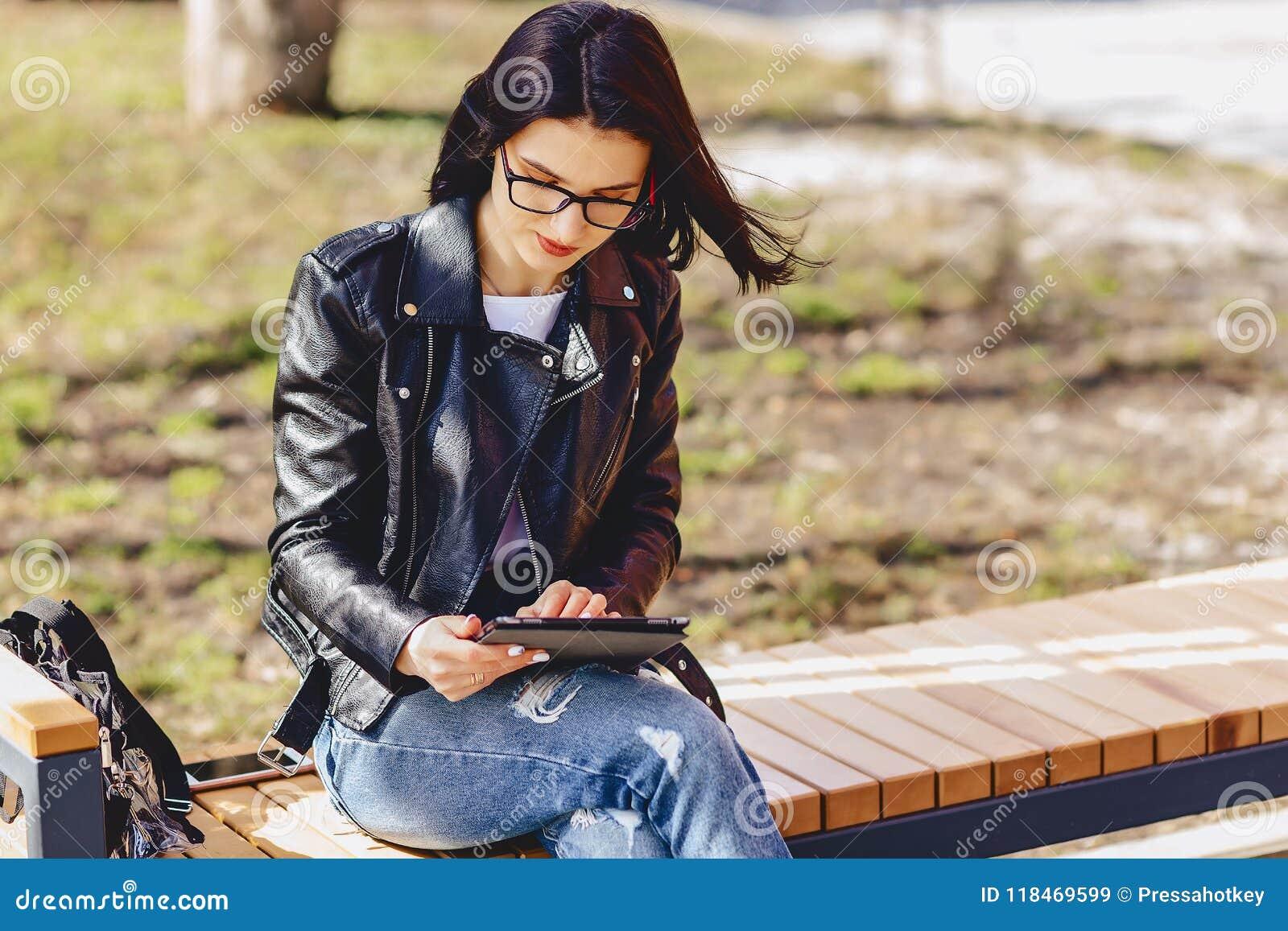 Ragazza attraente in vetri con la compressa al parco