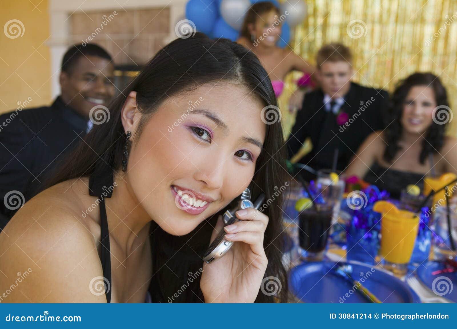 Ragazza ben vestito dell adolescente che per mezzo del telefono cellulare al ballo della scuola