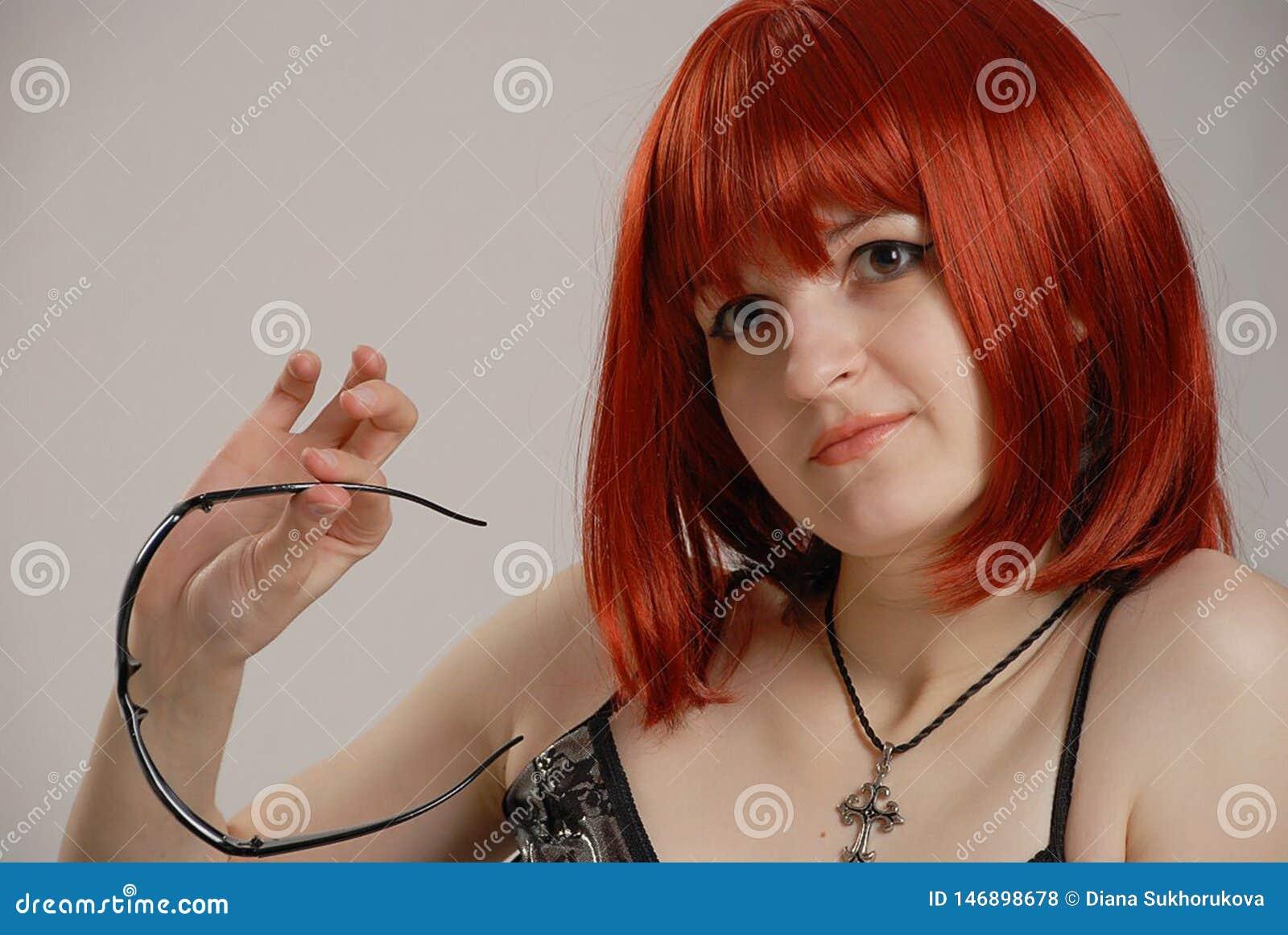 Ragazza bianca pensierosa dai capelli rossi con sorridere di vetro