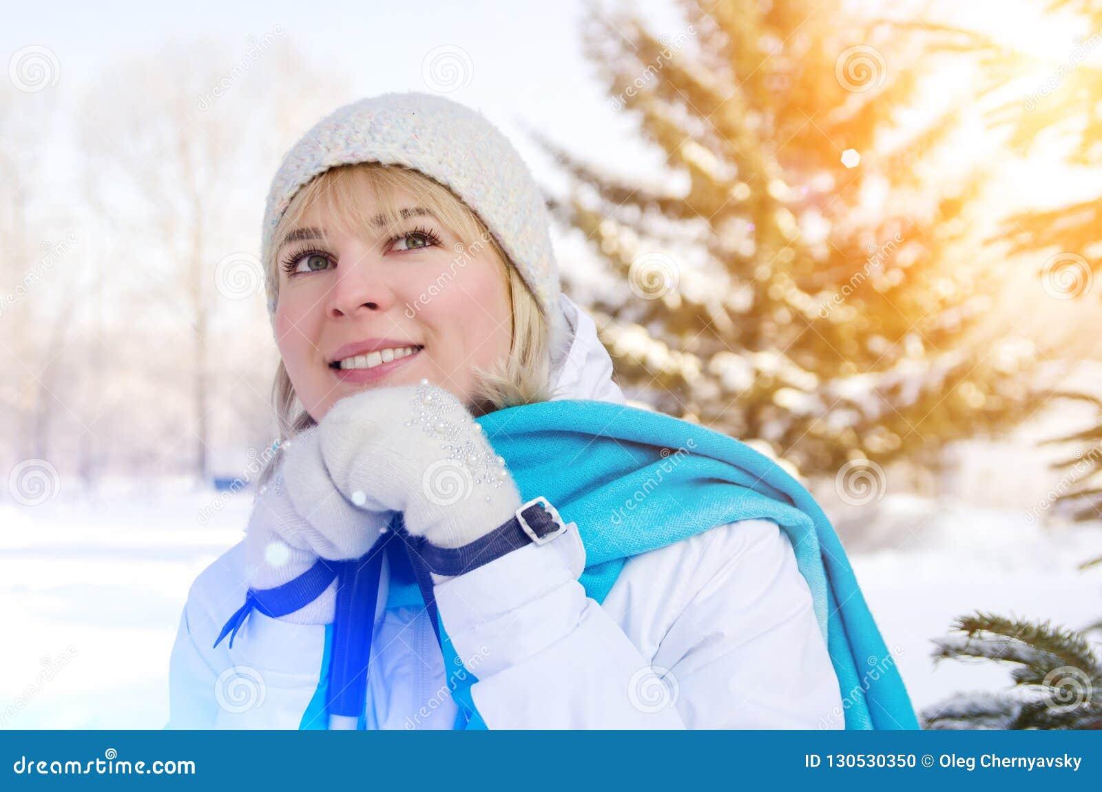 Ragazza bionda attraente con un sorriso con i pali di sci in mani