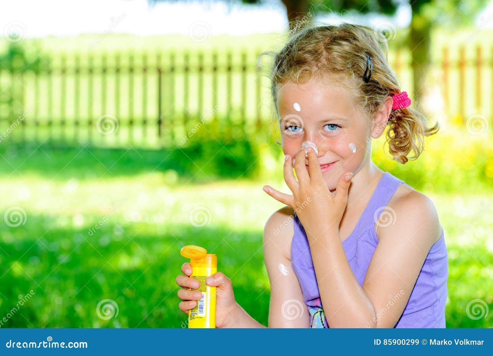 Ragazza bionda che utilizza la crema del sole nel giardino - Il sole nel giardino ...