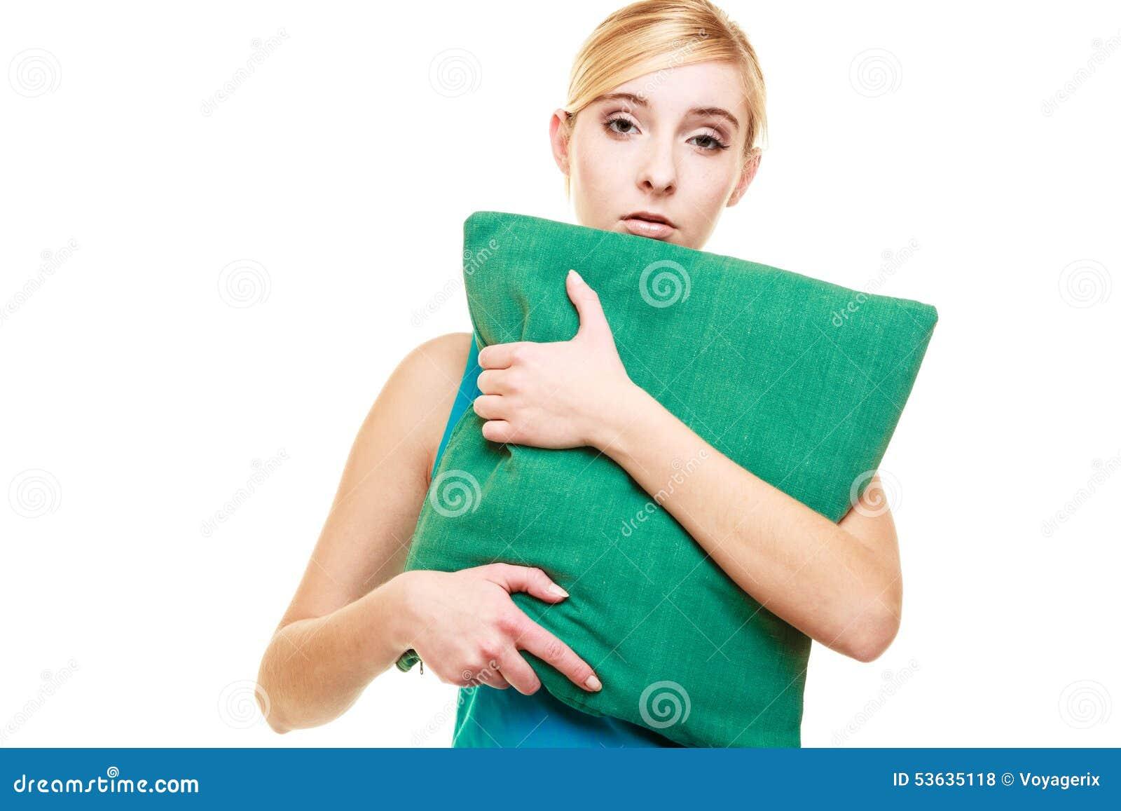 Ragazza bionda stanca sonnolenta con il cuscino verde