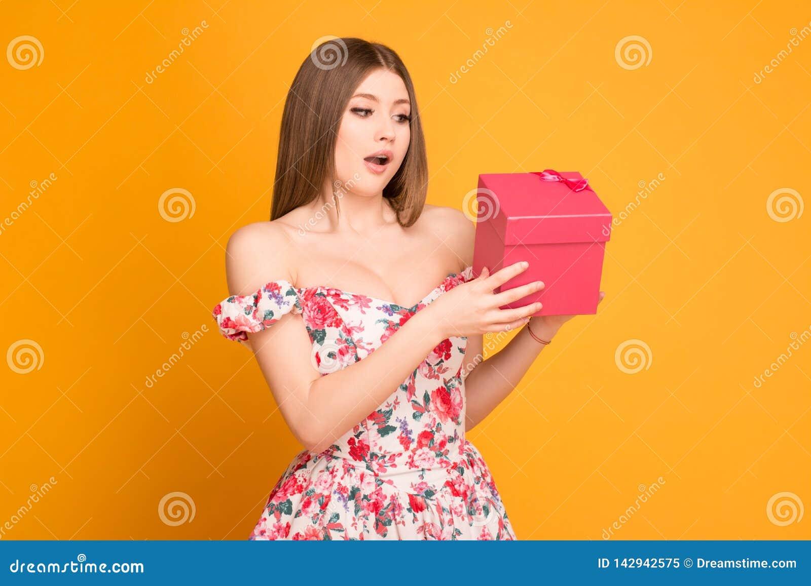 Ragazza bionda in un vestito che tiene un contenitore di regalo in sue mani
