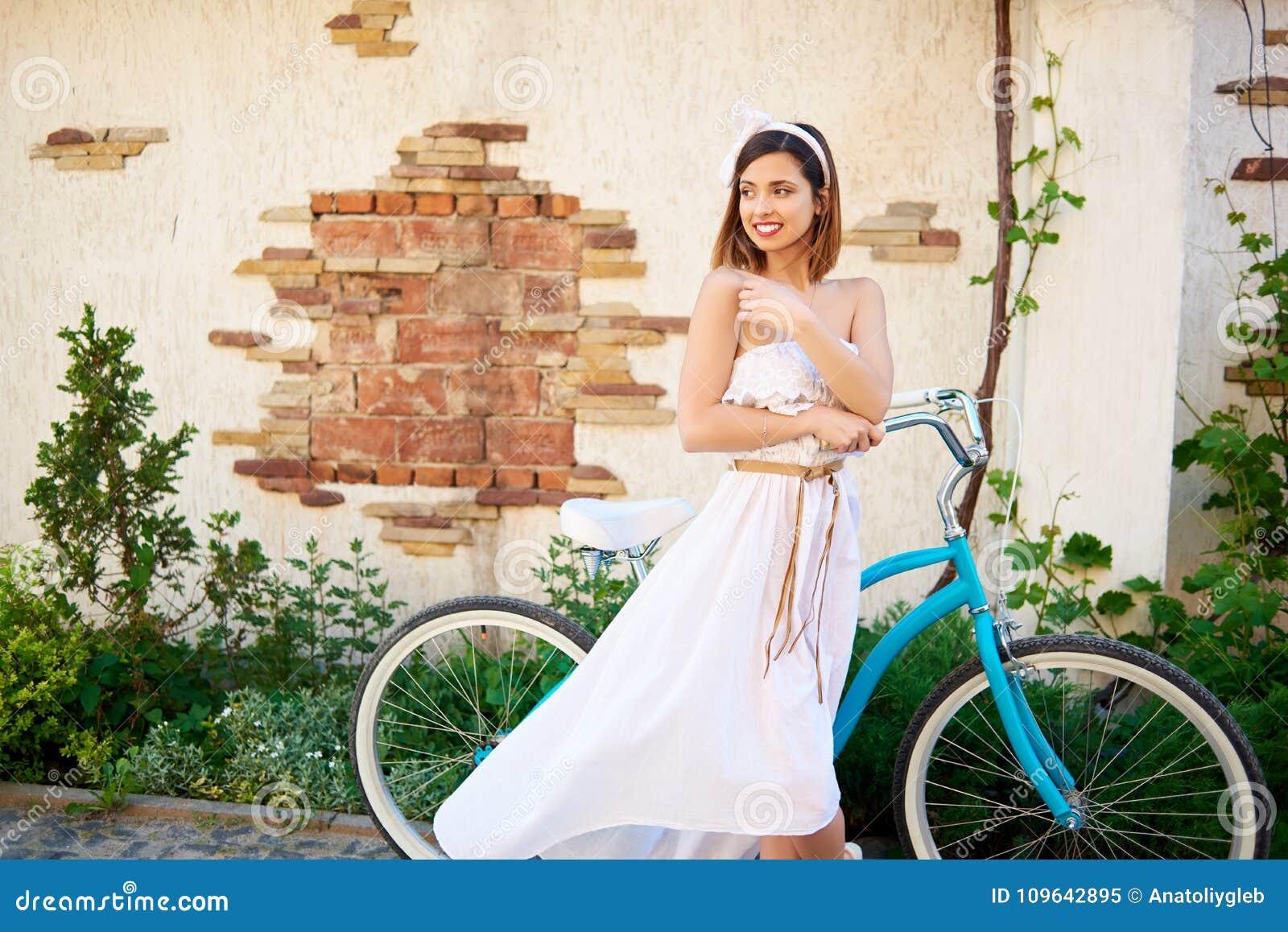 Ragazza castana attraente che posa vicino alla bici blu davanti alla vecchia costruzione di mattone
